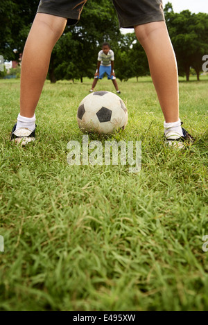 Children playing soccer game in park, with copy space on grass and focus on football ball - Stock Photo