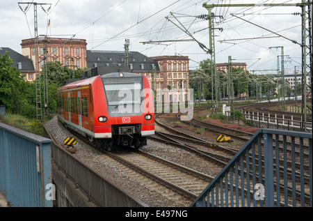 A suburban train operated by Deutsche Bahn passed the Schloss in Mannheim before crossing the Konrad-Adenauer Brücke - Stock Photo