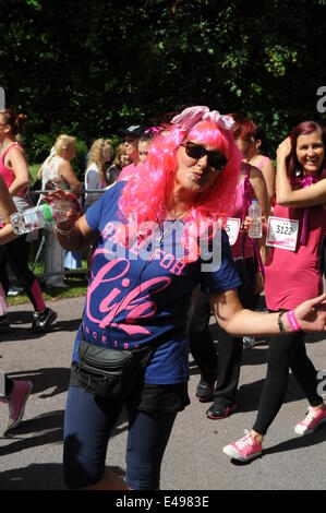 Liverpool, UK. Sunday 6th July 2014. Woman in a long pink wig blows a kiss. Cancer Research UK's Race for Life is - Stock Photo