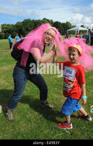 Liverpool, UK. Sunday 6th July 2014. Mother and son prepare for race. Cancer Research UK's Race for Life is a series - Stock Photo