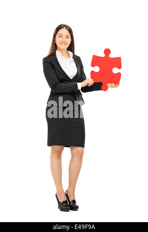 Full length portrait of a businesswoman holding a piece of a puzzle - Stock Photo