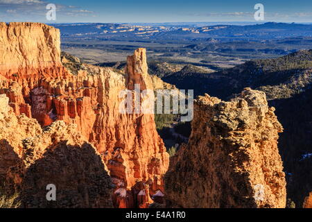 Cliffs and hoodoos lit by late afternoon sun with distant view in winter, Paria View, Bryce Canyon National Park, - Stock Photo