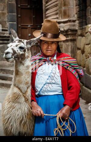 Portrait of a Quechua woman with llama along an Inca wall in San Blas neighborhood, Cuzco, Peru, South America - Stock Photo