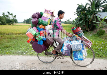 Young village tradesman cycling with a large load of plastic houseware, Majuli, Assam, India, Asia - Stock Photo