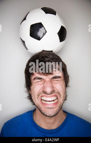 Young man balancing soccer ball on head - Stock Photo
