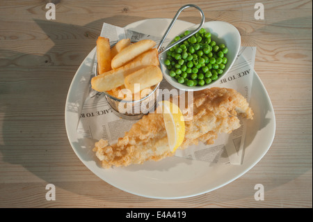 Fish and chips (Haddock in batter) with peas and a segment of lemon on a white plate on a wooden table. - Stock Photo