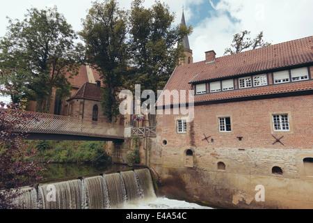Germany, North Rhine-Westphalia, Telgte, Dam at mill and Saint Clemens parish church - Stock Photo