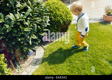 Little boy finding an Easter surprise in the garden - Stock Photo