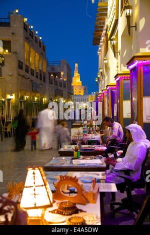 Souq Waqif looking towards the illuminated spiral mosque of the Kassem Darwish Fakhroo Islamic Centre, Doha, Qatar, - Stock Photo