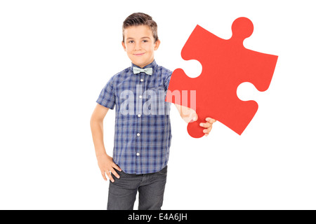 Little kid holding a piece of a puzzle - Stock Photo