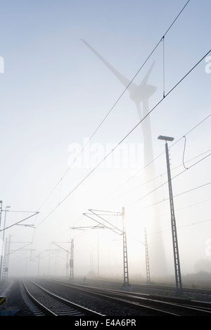 Germany, Hamburg, wind turbine next to railway track in early morning fog - Stock Photo