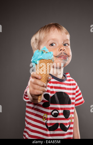 Portrait of little boy with painted beard and ice cream - Stock Photo