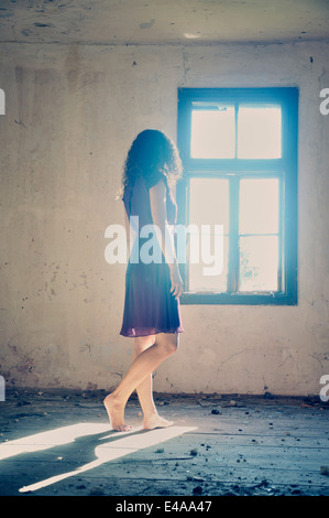 Young woman standing by the window - Stock Photo