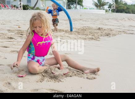 a blond, five year old girl plays with a sand mold while her 2 year old brother runs toward her holding a water - Stock Photo