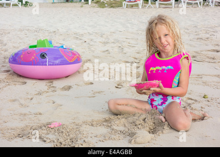 A blond, smiling Caucasian 5 year old girl holding a sand mold, plays on Sandcastle Beach in St. Croix, U.S. Virgin - Stock Photo