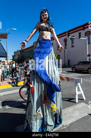 Circus performer on stilts entertain visitors enjoying artwork during the annual small town ArtWalk Festival - Stock Photo