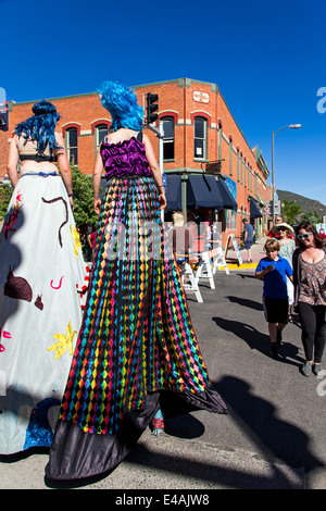 Circus performers on stilts entertain visitors enjoying artwork during the annual small town ArtWalk Festival - Stock Photo
