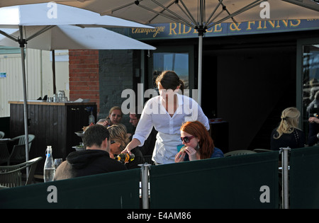 Waitress pouring wine to customers sitting outside at Riddle & Finns restaurant on Brighton seafront beach UK