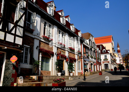 BAI LU, CHINA: View looking north on the principal street of the Sino-French village with its handsome French Alsatian - Stock Photo