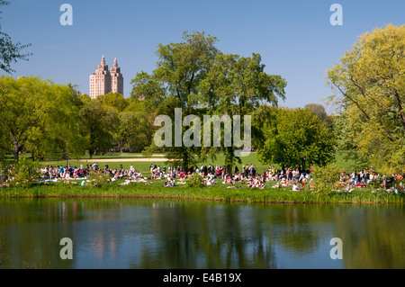 People relaxing next to Turtle Pond in Central Park, NYC on a warm spring day. - Stock Photo