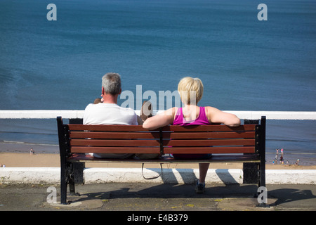 Mature couple sitting on bench overlooking Saltburn beach. Saltburn by the sea, North Yorkshire, England, UK Stock Photo