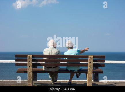 Elderly couple sitting on bench overlooking sea. UK Stock Photo