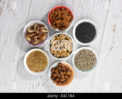 a selection of four different types of nuts and three types of seeds in bowels on a white wooden background - Stock Photo