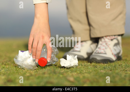 Eco hiker hand collecting garbage in the grass of the mountain - Stock Photo
