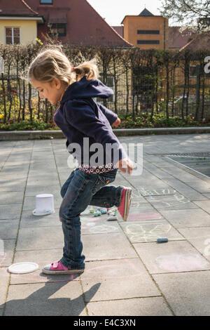 Blonde girl playing hopscotch on sidewalk, Munich, Bavaria, Germany - Stock Photo
