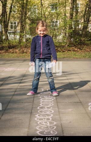 Blonde girl drawing with chalk on sidewalk, Munich, Bavaria, Germany - Stock Photo