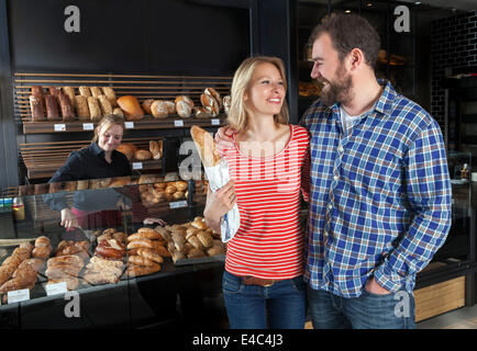 Couple in bakery buys fresh bread, shop assistant in background - Stock Photo