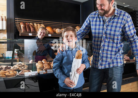 Father and son buying bread in a bakery - Stock Photo