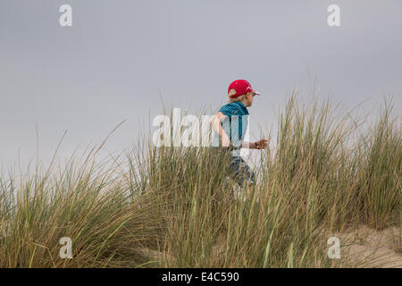Young Boy running through the Dunes - Stock Photo