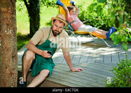 Man using smartphone, boy relaxing in the background, Munich, Bavaria, Germany - Stock Photo