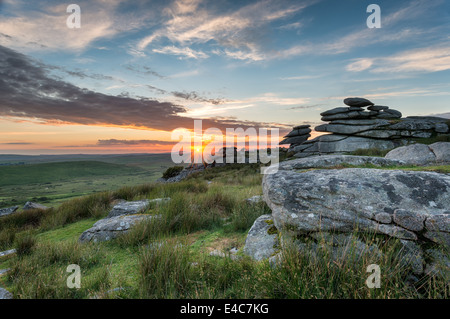Beautiful sunset over a granite tor at the Cheesewring on Stowes Hill near the Minions on Bodmin Moor in Cornwall - Stock Photo