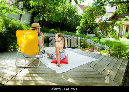 Heterosexual couple takes a break by the pond, Munich, Bavaria, Germany - Stock Photo