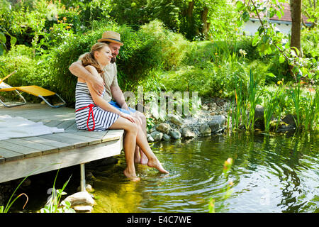 Heterosexual couple takes a break by the pond, rear view, Munich, Bavaria, Germany - Stock Photo