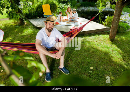 Man relaxing on hammock, family in background, Munich, Bavaria, Germany - Stock Photo