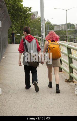 Teenage couple holding hands walking home from school in Brooklyn, NY. - Stock Photo