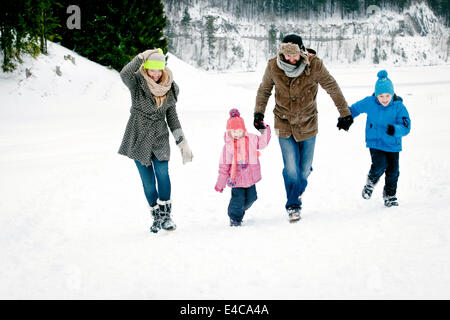 Family with two children in snow-covered landscape having fun, Bavaria, Germany - Stock Photo