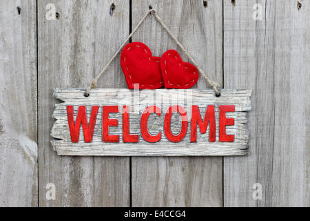 Rustic wood welcome sign with red hearts hanging on wooden fence - Stock Photo