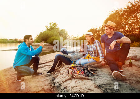 Group of friends taking pictures by campfire on riverbank, Osijek, Croatia - Stock Photo