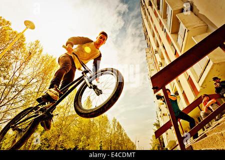 BMX biker performing a stunt over a railing - Stock Photo