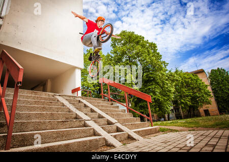 BMX biker performing a stunt over a staircase - Stock Photo