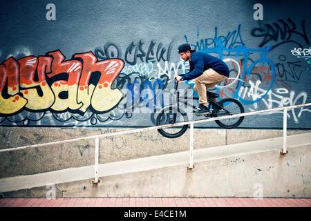 BMX biker riding down a ramp - Stock Photo