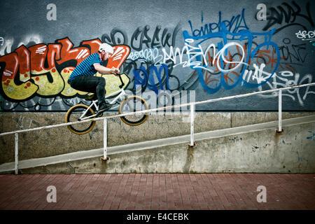 BMX biker performing a stunt on a railing - Stock Photo