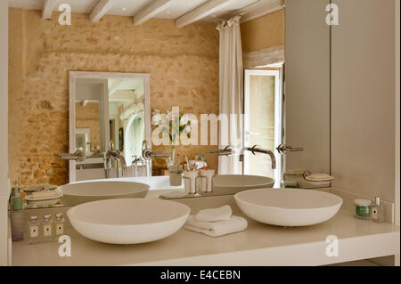 Twin Spoon CER 700 basins by Agape in bathroom with rough stone walls - Stock Photo
