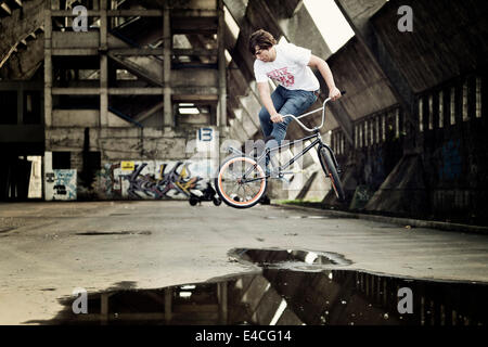 BMX biker performing a stunt over a puddle - Stock Photo