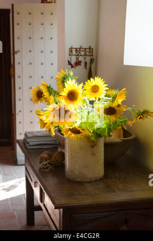 Jug of sunflowers on old wooden console table in entrance hall with studded door and terracotta tiled floor - Stock Photo