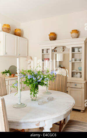Distressed white dining table in Provencal style country kitchen with french dresser - Stock Photo